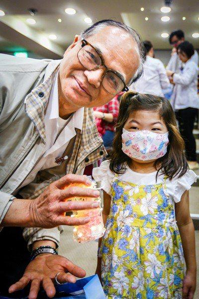 亞東醫院舉辦「懷恩節」追思器官捐贈者典禮,器官受贈者姚小妹(右)送上永生花感謝捐...