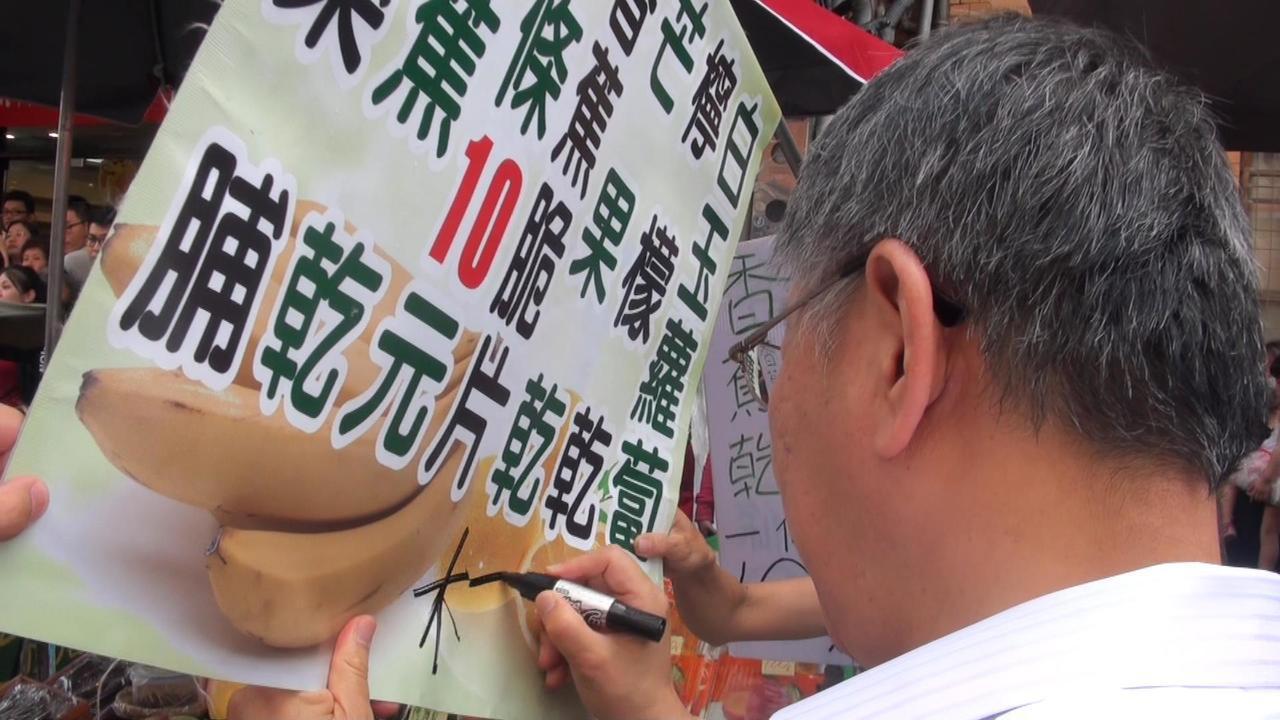 柯文哲在旗山老街攤商的招牌上簽名。記者王昭月/攝影