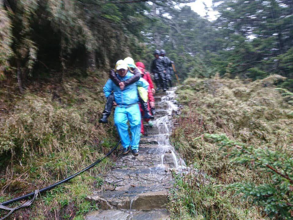 兩名雲豹隊員在風雨中輪流背負女山友,走了8.4公里山路到玉山登山口,將傷患送醫救...