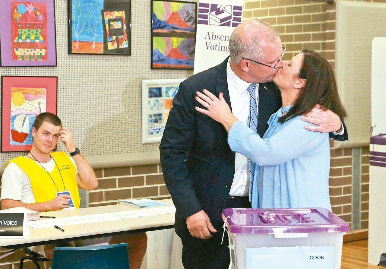 澳洲總理莫里森十八日投完票後與妻子珍妮當眾曬恩愛,選務人員表情尷尬。 (美聯社)