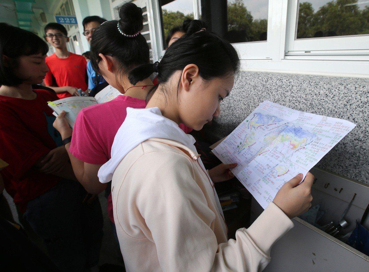 21萬多人報名的國中會考上午登場,建中考場裡,一名考生看著筆記做最後衝刺。 記者...