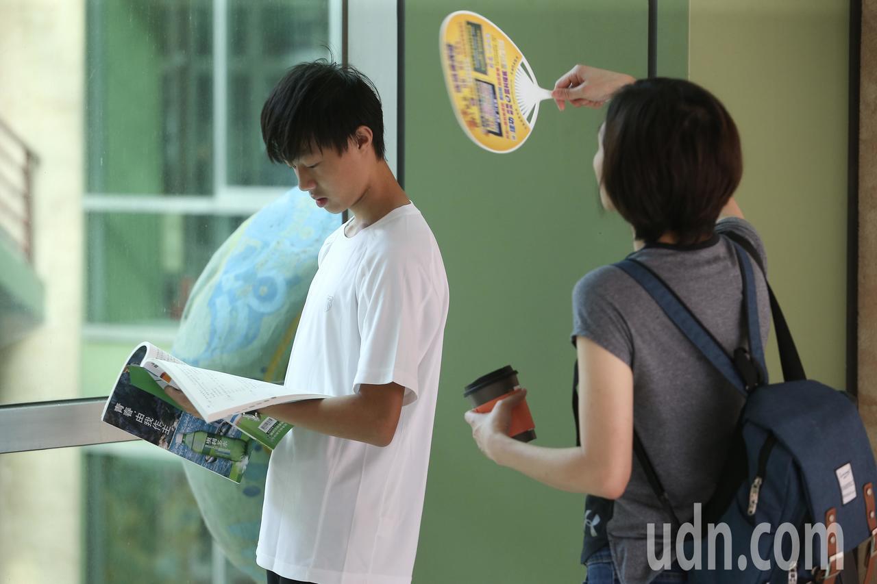 108年國中教育會考上午進行第二天考試,考生家長在考前拿著扇子,幫在做最後複習的...