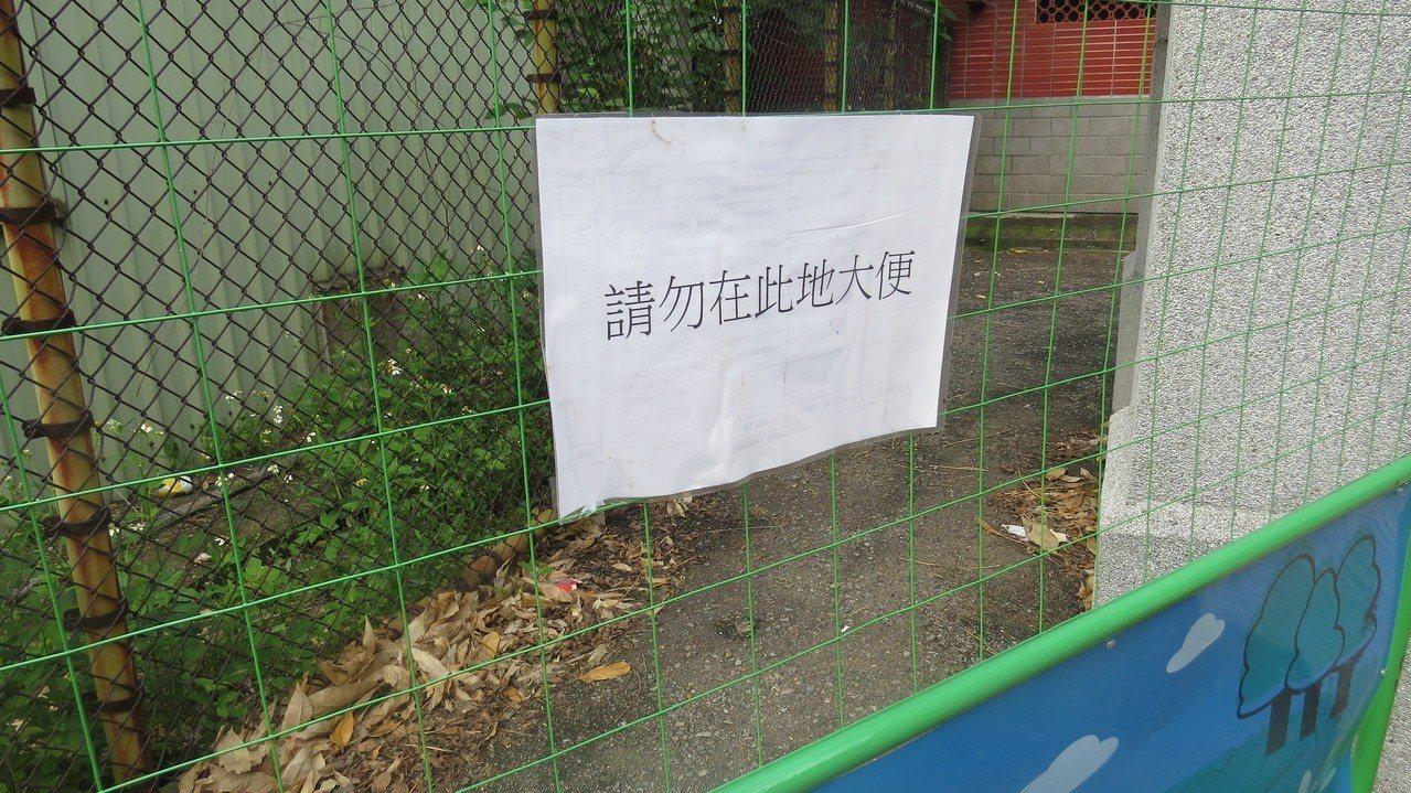 苗栗火車站鐵道一村廣場對面公廁邊小路圍籬,告示請勿在此地大便。記者范榮達/攝影
