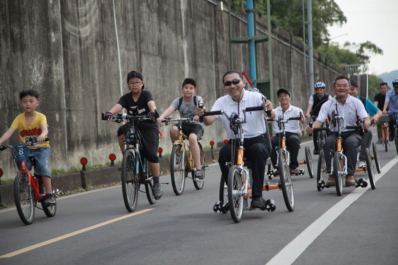 侯友宜與身心障礙者一起駕駛手搖車到大漢橋,再換騎乘自行車一路到華江橋,並欣賞沿途...