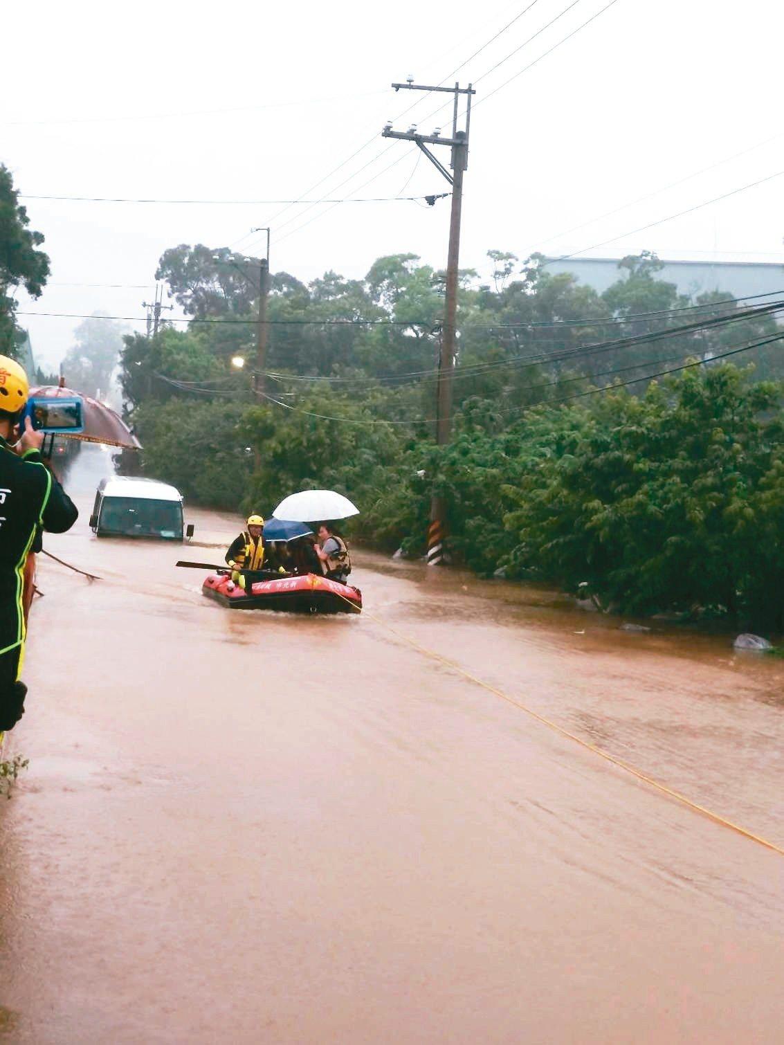 消防人員出動船艇到石門區,帶離因淹水受困的小型巴士民眾。 圖/新北巿消防局提供