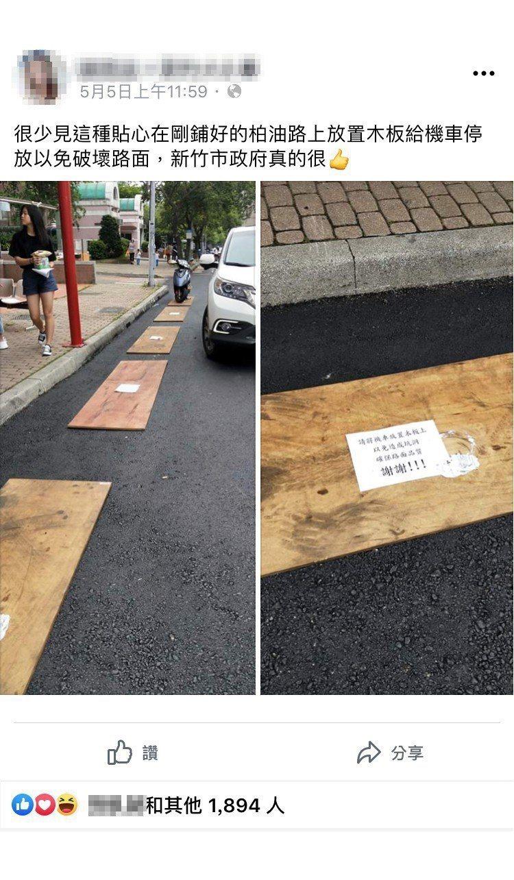 新竹市府工務處在剛鋪好的柏油路上放置木板給機車停放,除了避免破壞路面,也讓機車免...