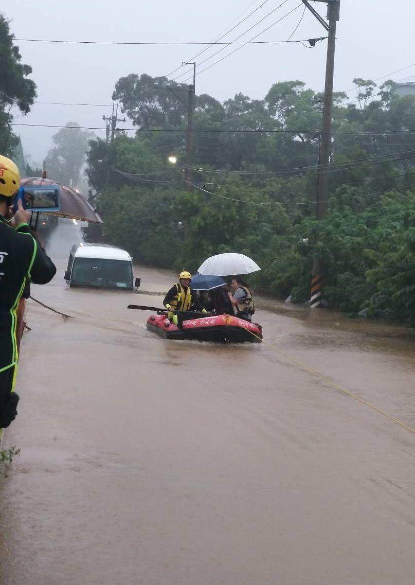 消防隊出動橡皮艇將受困民眾接回安全區域。圖/新北市消防局提供