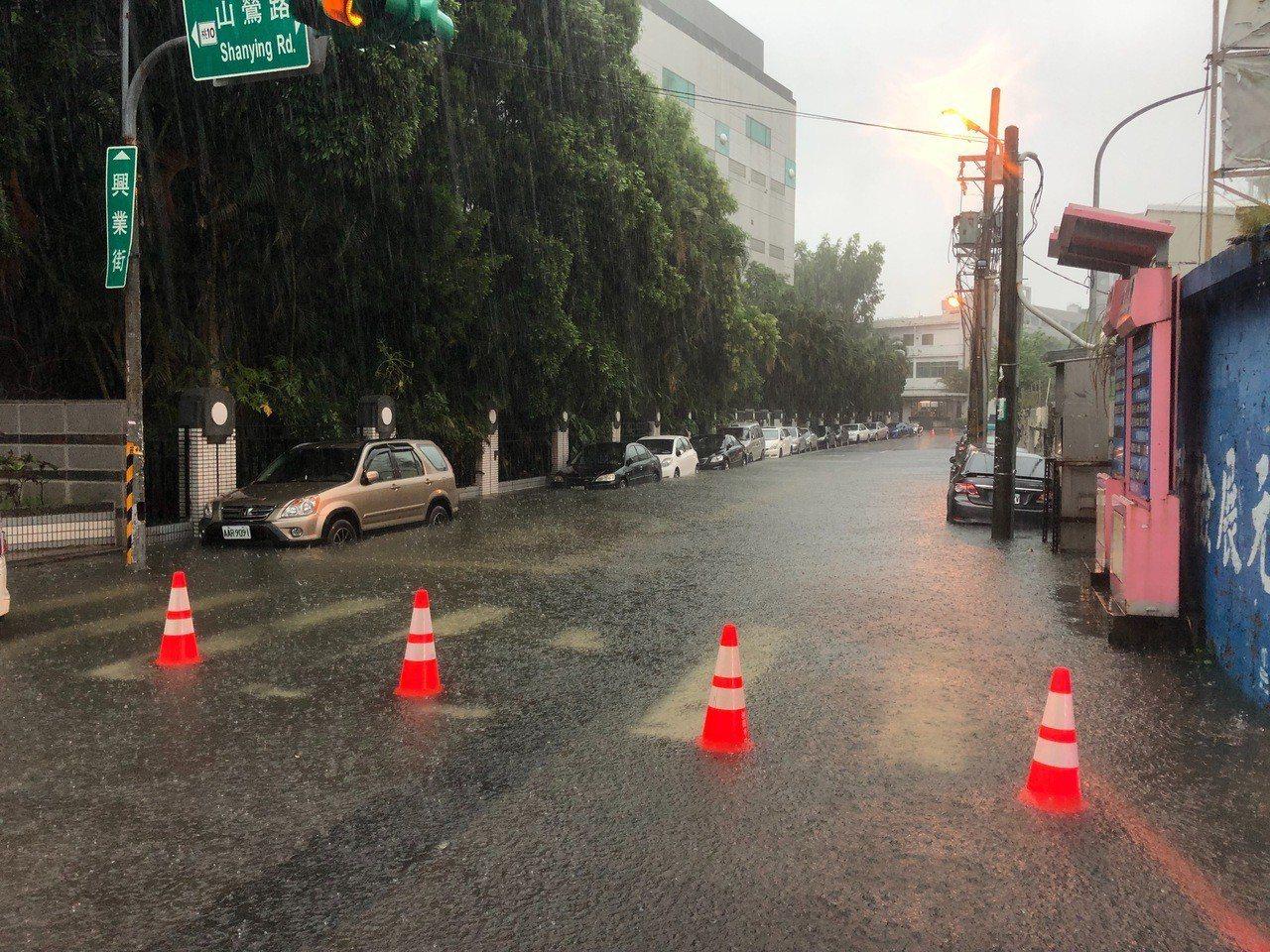 桃園市龜山區興業街淹水約20公分,警方已用交通錐封閉,並派員協助疏導管制中。圖/...