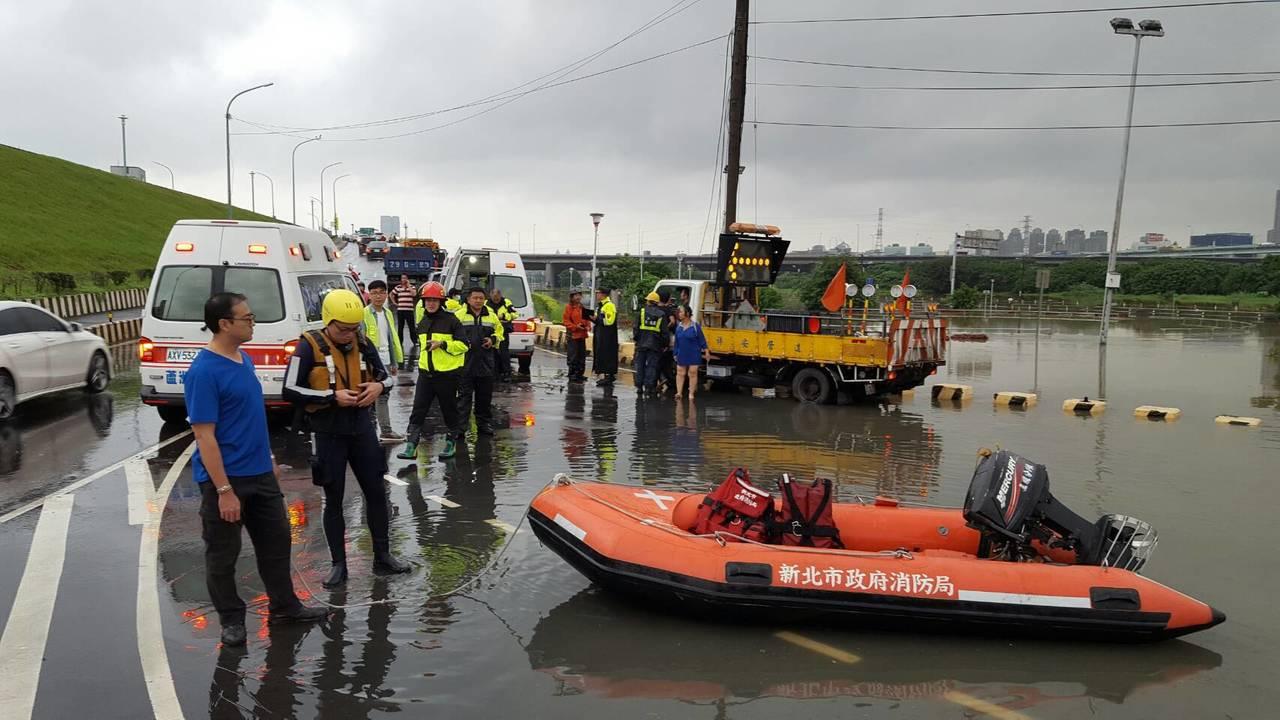 疏洪道積水及腰,消防隊出動橡皮艇陸續救出6名受困民眾。圖/新北市消防局提供