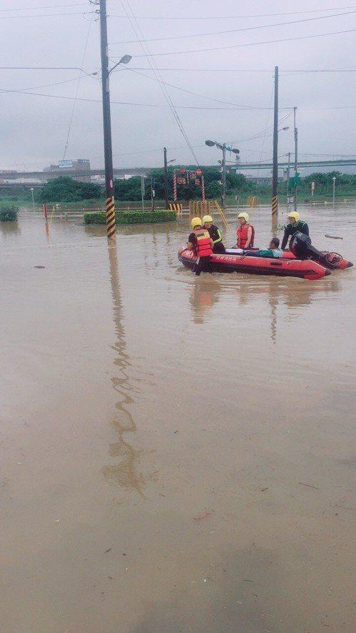 疏洪道積水及腰,消防隊出動橡皮艇陸續救出6名受困民眾。圖/蘆洲警分局提供