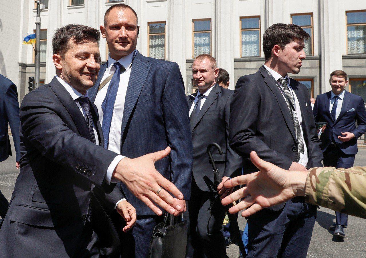 澤倫斯基就職後從國會走到總統府,途中與支持者握手。(路透)