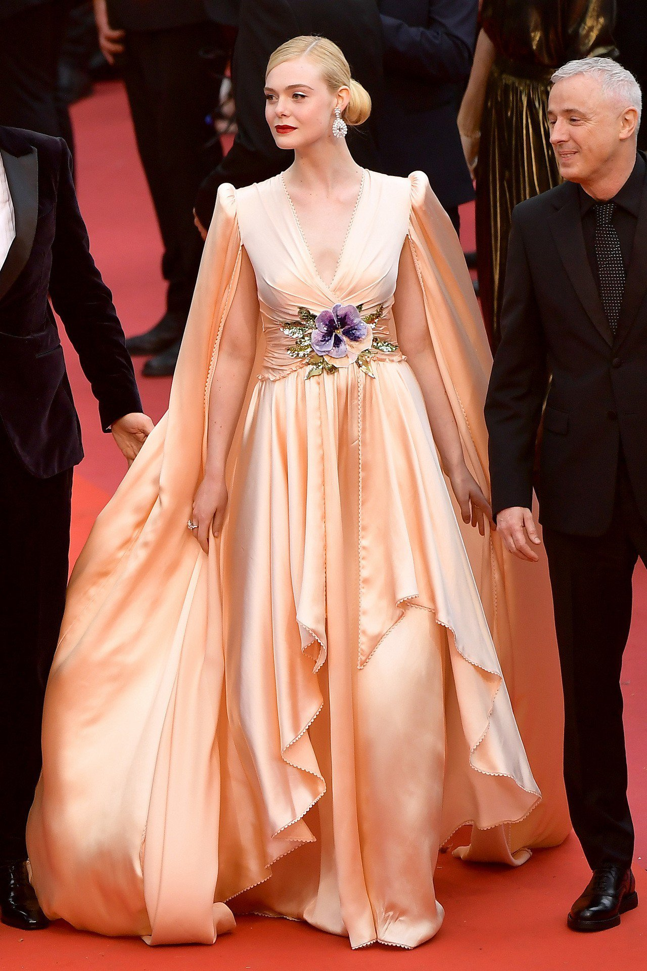 艾兒芬妮穿著Gucci粉色絲綢斗篷禮服,腰部飾以紫色和象牙白花卉刺繡,搭配裸色厚...