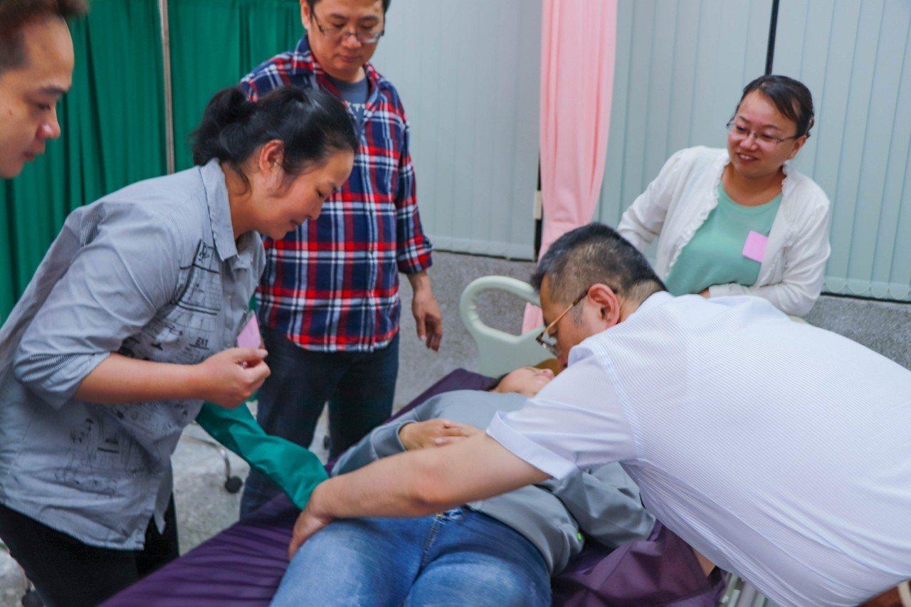日本老師印南裕之(右一)指導學員利用手套將病患移位。記者謝恩得/翻攝