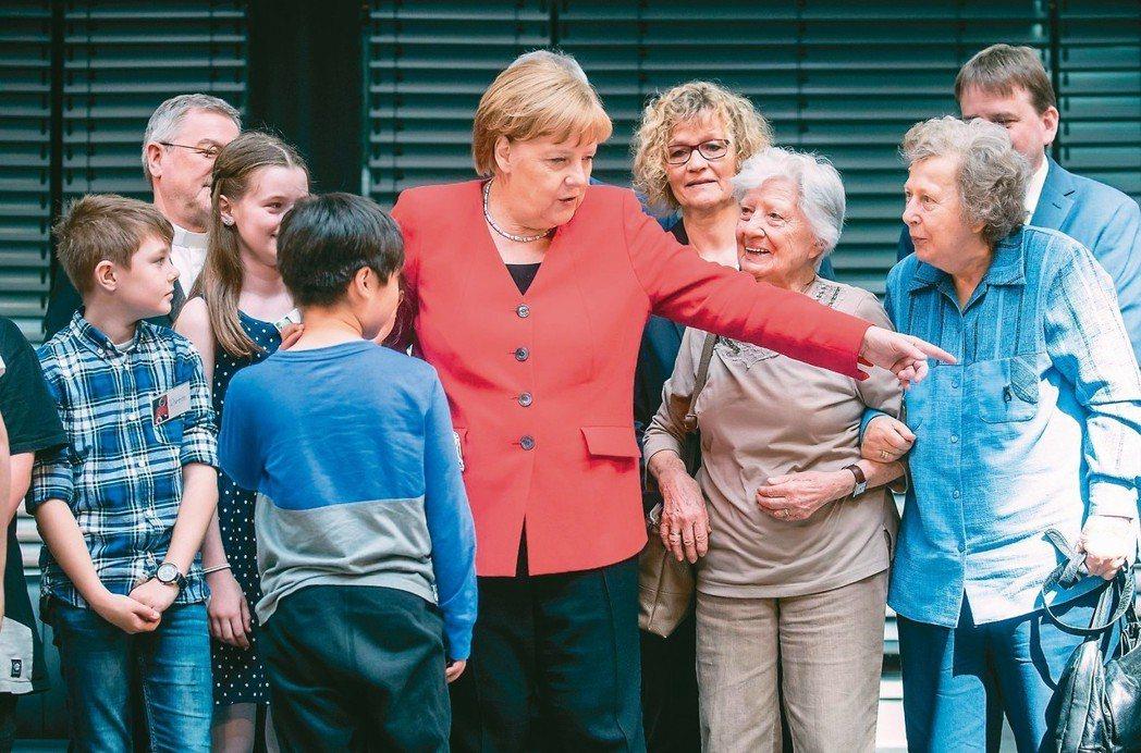 德國版「青銀同聚」 德國總理梅克爾(中)廿一日在柏林布蘭登堡門附近參加長者與青少...