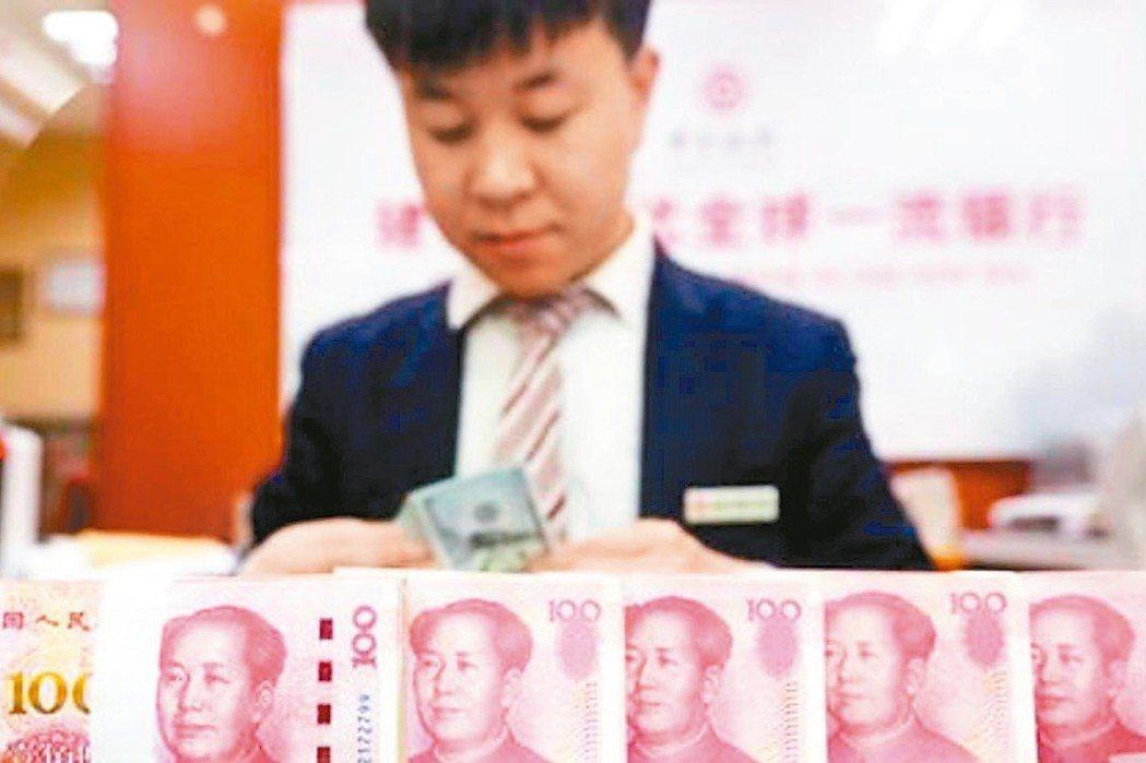 人行將再次在香港發行離岸央票。圖為銀行行員在清點鈔票。 中新社