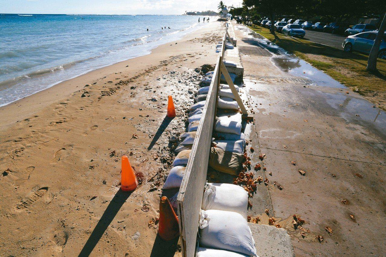 最新研究顯示,全球海平面的上升幅度可能遠超過預期,圖為夏威夷海灘以沙包阻擋大浪。...