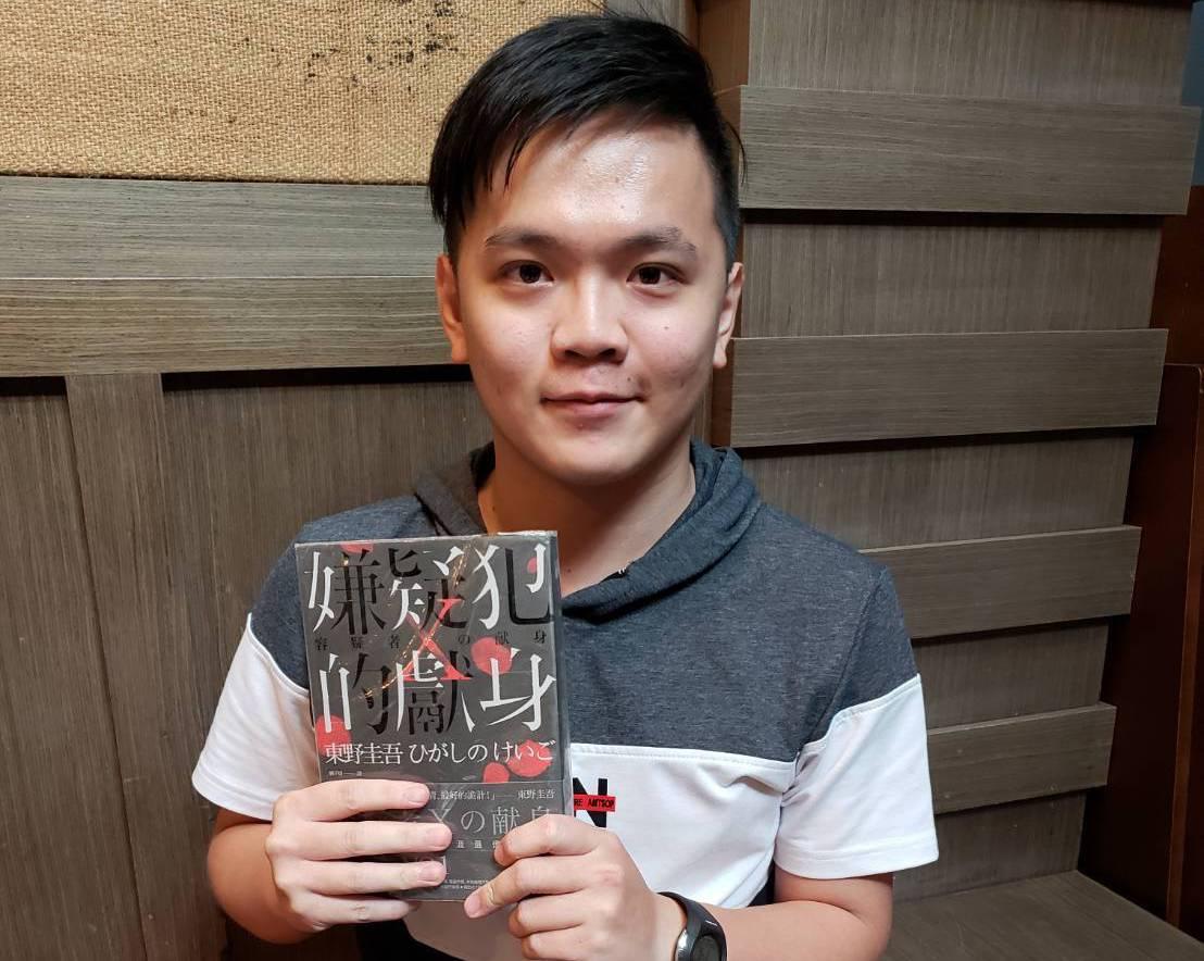 讀創故事作家孤煙仁心捧著東野圭吾作品《嫌疑犯X的獻身》,這本小說是啟發他成為作家...