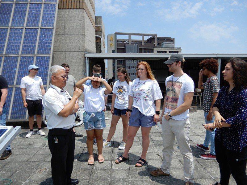健行科大電機系教授呂文隆(左)為美國阿帕契州立大學師生講解太陽光電基地功能。圖/健行科大提供