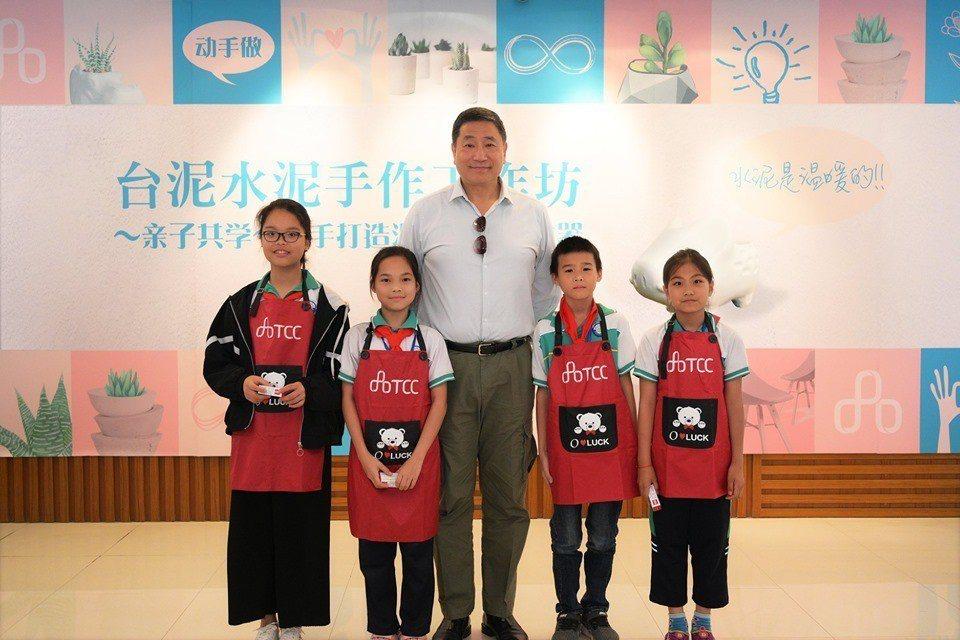 台泥公司董事長張安平,與廣西貴港廠旁的大郭小學小朋友一起合照。取自╱台泥集團臉書