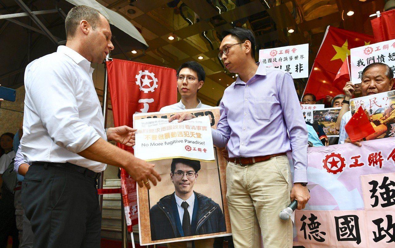香港工聯會23日遊行到德國駐香港總領事館,抗議德國包庇旺角暴亂疑犯,要求德國尊重...