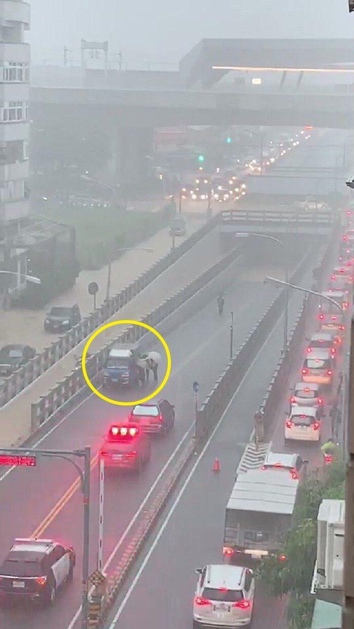 台中暴雨造成太原地下道龐婦駕駛的小貨車拋錨,五名員警(黃色圓圈處)合力將貨車推至...