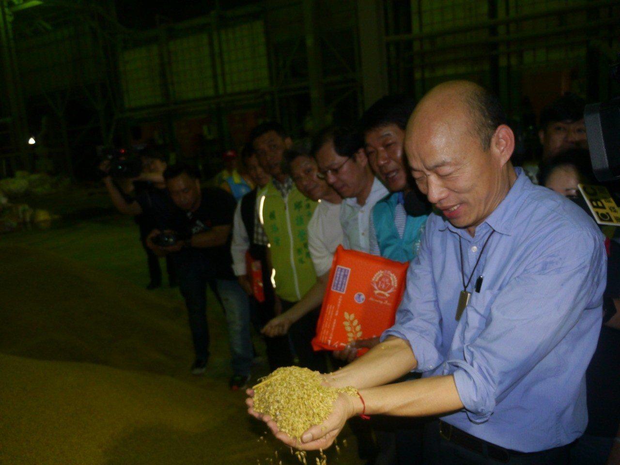 高雄市長韓國瑜捧起農民繳交的稻穀觀看。記者徐白櫻/攝影