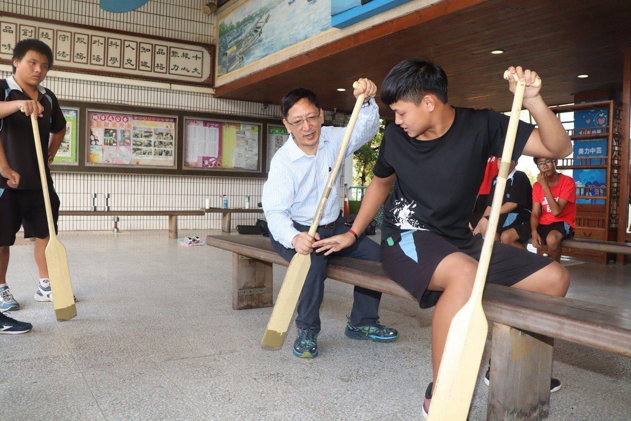 中芸國中學生教育局長吳榕峯如何正確用槳划傳統龍舟。