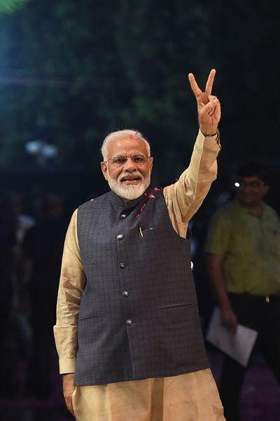 印度總理莫迪23日在新德里人民黨總部比出勝利手勢。(法新社)