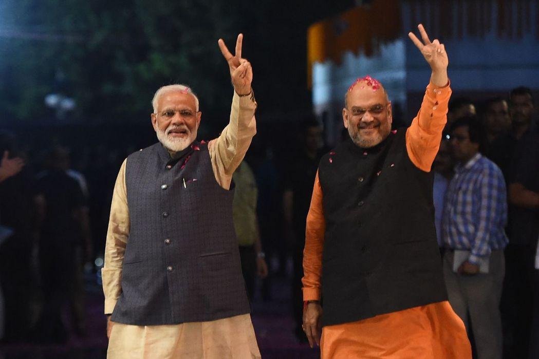 印度總理莫迪(左)與軍師夏哈(右)23日在人民黨總部比出勝利手勢。(法新社)