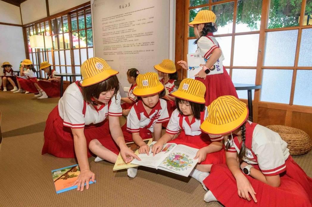 陽光書屋」以「櫻桃小丸子」為主題背景,打造親子共讀空間。圖為志工媽媽陪伴學童閱讀...