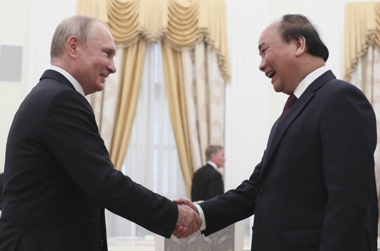 俄羅斯總統普亭(左)日前在克里姆林宮接見了越南總理阮春福(右)率領的參訪團。(美...