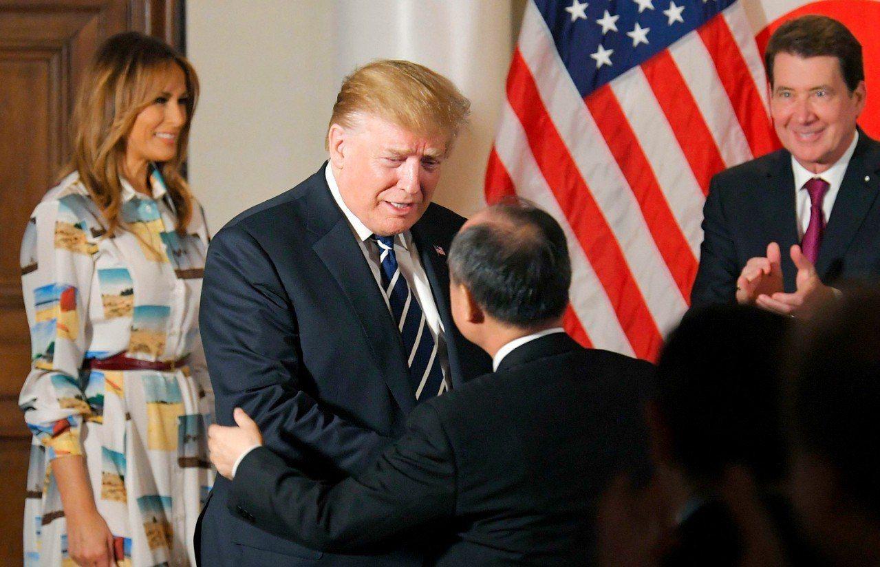 美國總統川普25日飛抵訪日,與包括軟銀董事長孫正義(圖中右)在內的40位日本企業...
