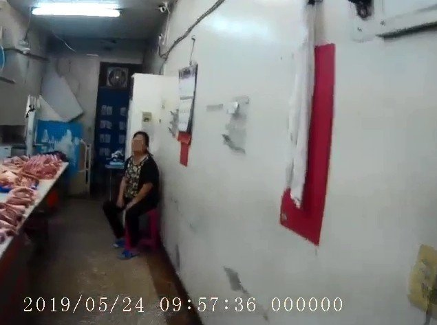 70歲李婦罹患失智症,坐在豬肉攤內等待員警到場。記者林佩均/翻攝