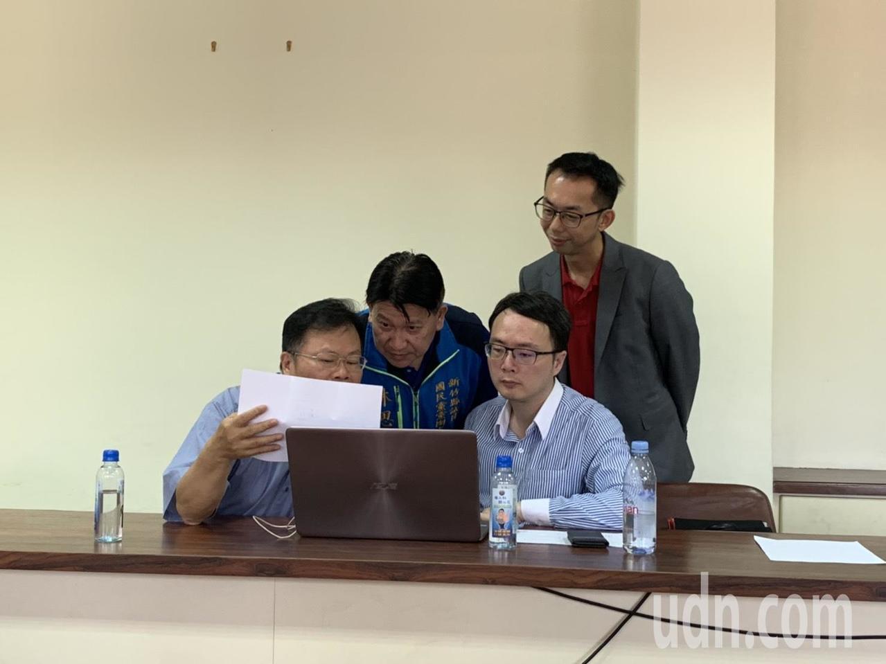 國民黨新竹縣立委第二選區參選人林思銘(左二)、邱一峰(後排)正在核對民調結果有無...