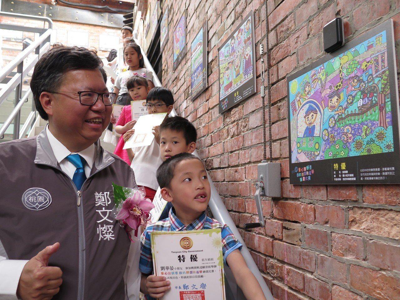 建德國小一年級學生劉華晏(右)以「我的快樂號捷運」畫作拿下特優,市長鄭文燦(左)...