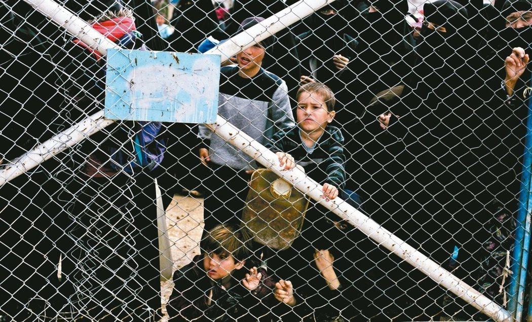 關在敘利亞阿霍難民營鐵門內的伊斯蘭國戰士外籍子女,無助向外張望。 (美聯社)