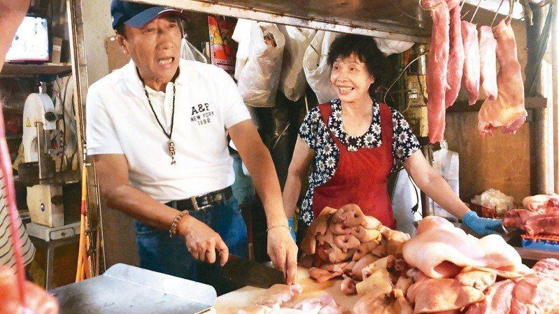 鴻海董事長郭台銘展現親民特質,還到攤商切豬肉。 記者李承穎/攝影
