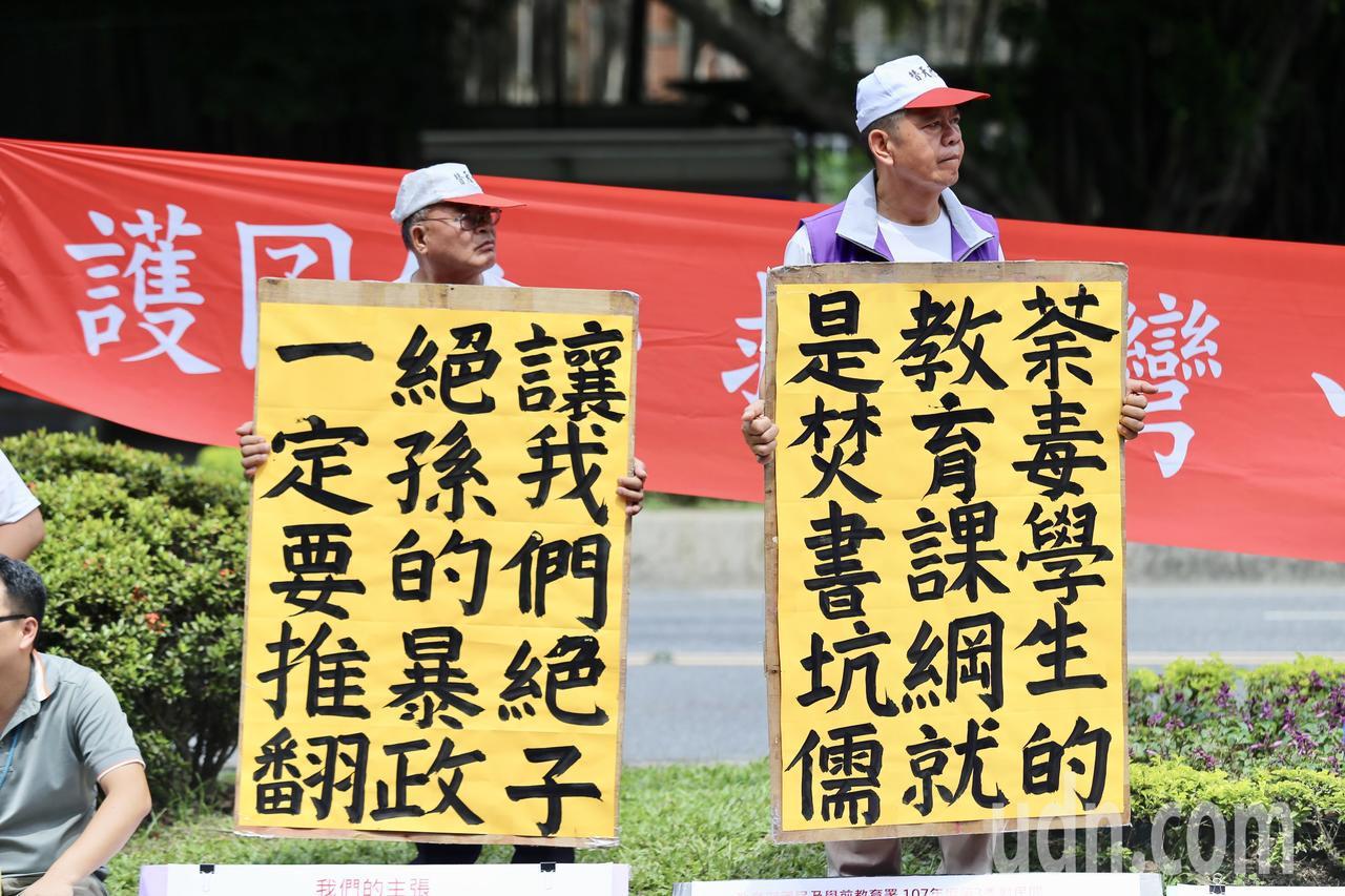 國教行動聯盟上午在教育部前舉行「護囝仔、救台灣、終結教改之亂」活動,手舉標語向教...