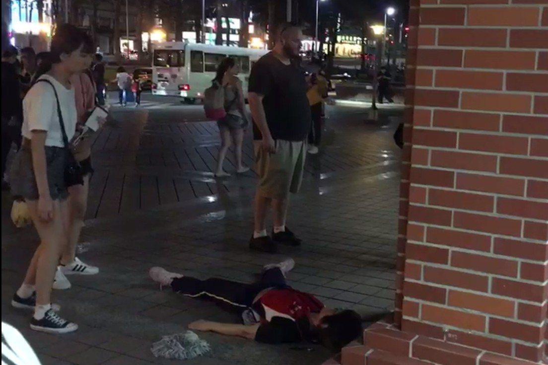莊姓女主管在人來人往的捷運站出口被打趴倒地不動,吸引許多旅客圍觀。記者林昭彰/翻...