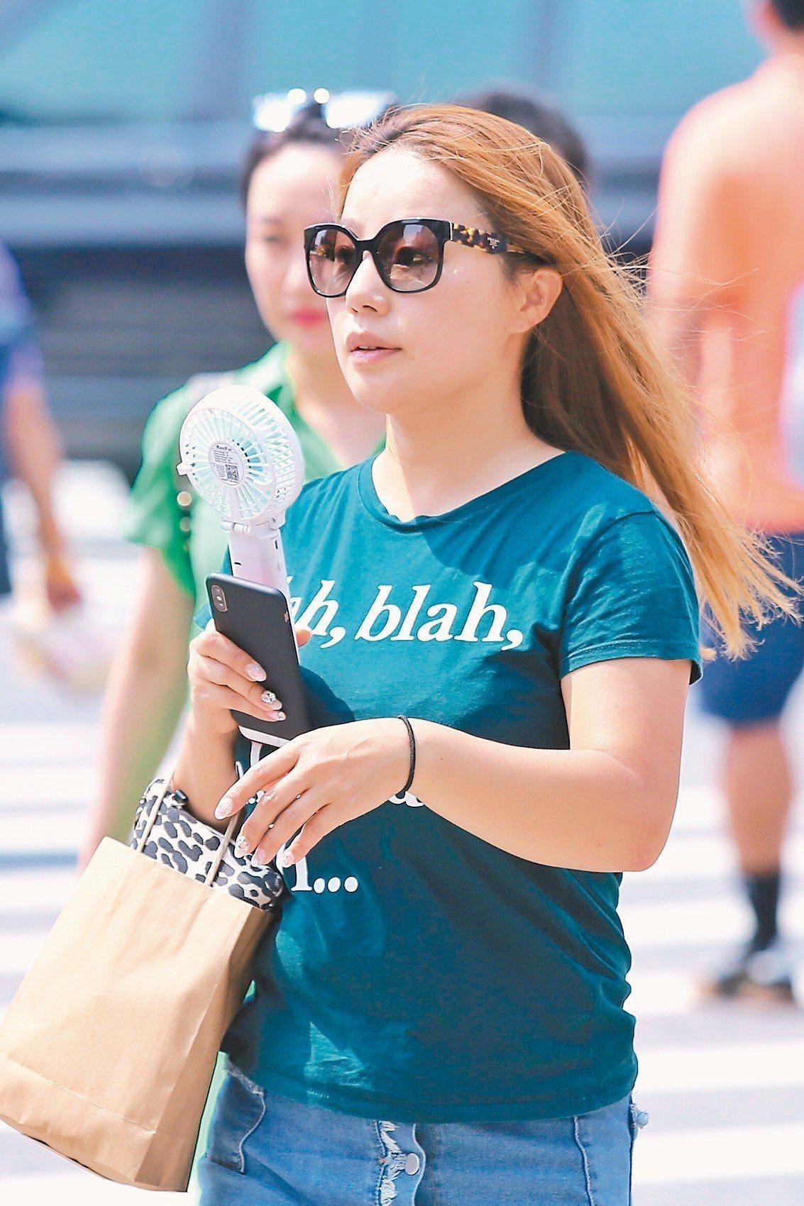 全台昨高溫炎熱,台北街頭有民眾自備小電扇消暑,但今起又有梅雨鋒面來襲。 記者林伯...