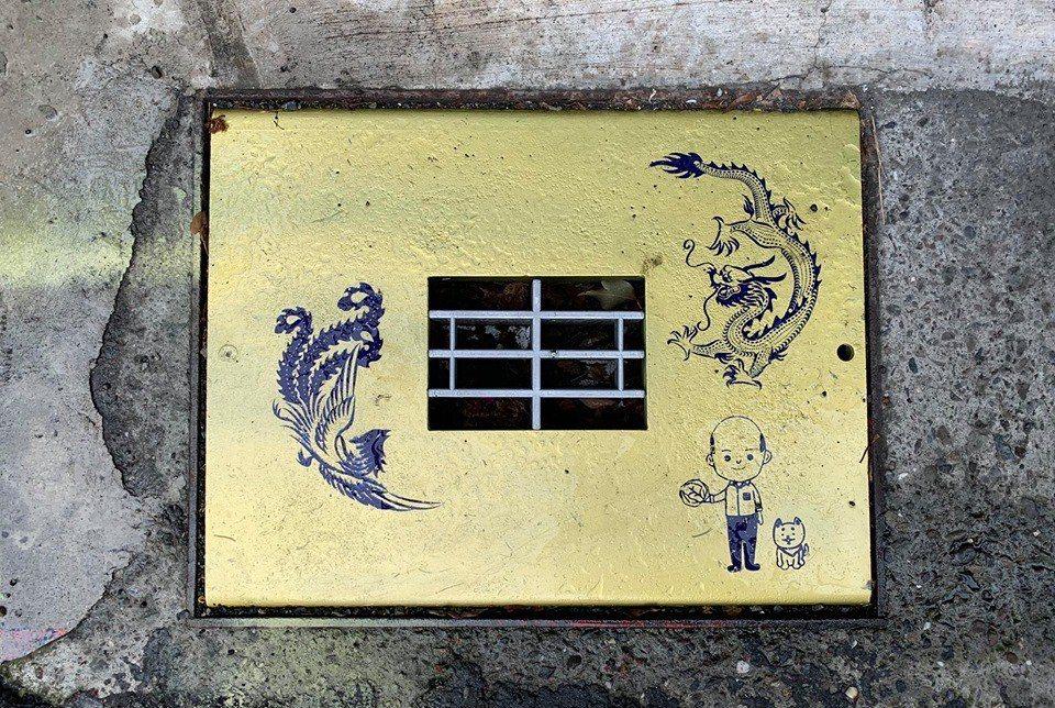 高市新興區德生里最近出現印有龍鳳、高市長韓國瑜牽著狗的圖樣的金色水溝蓋。圖擷自高...