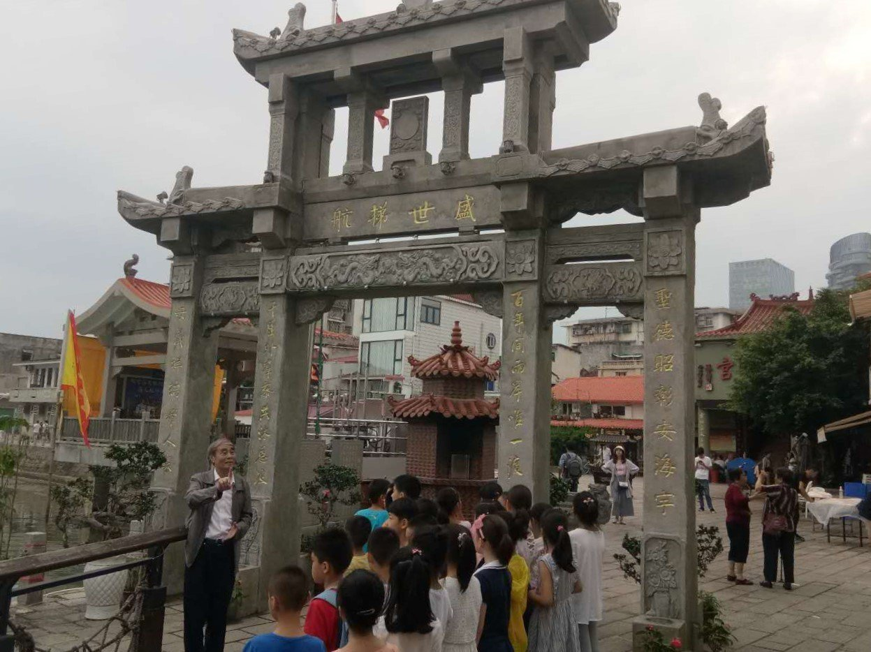 廈門著名文史專家彭一萬(左一)為孩子們和家長解說「盛世梯航」牌坊來由。廈門朝天宮...