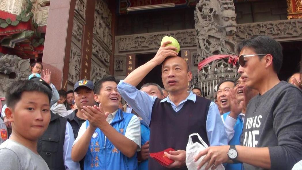 韓國瑜過年到大社發紅包,有民眾送他一顆大芭樂,韓順手頂到頭上展示。本報資料照