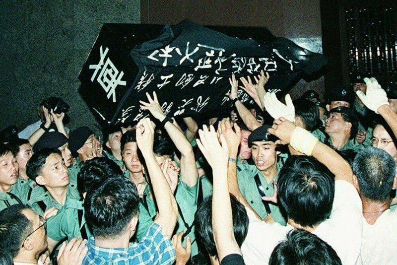 圖為1996年6月2日,香港民眾將黑棺材丟向新華社香港分社大門,當時這裡為中國派駐香港的官方代表機構。 圖/法新社