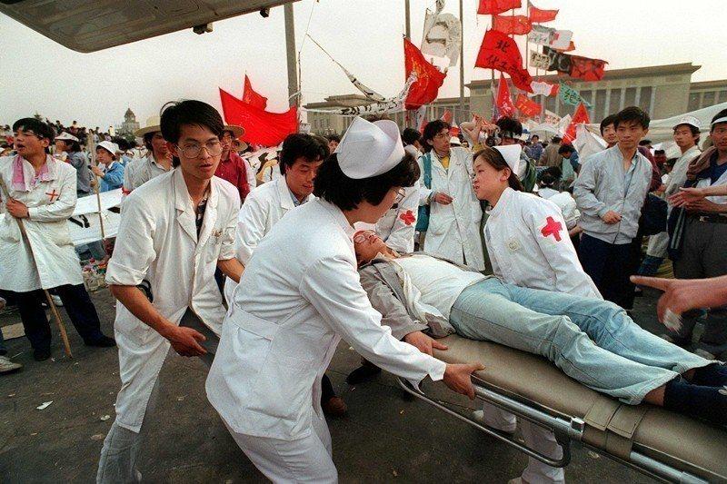 醫護人員正救助一名因絕食而暈倒的學生,攝於1989年5月17日,北京天安門。 圖/法新社