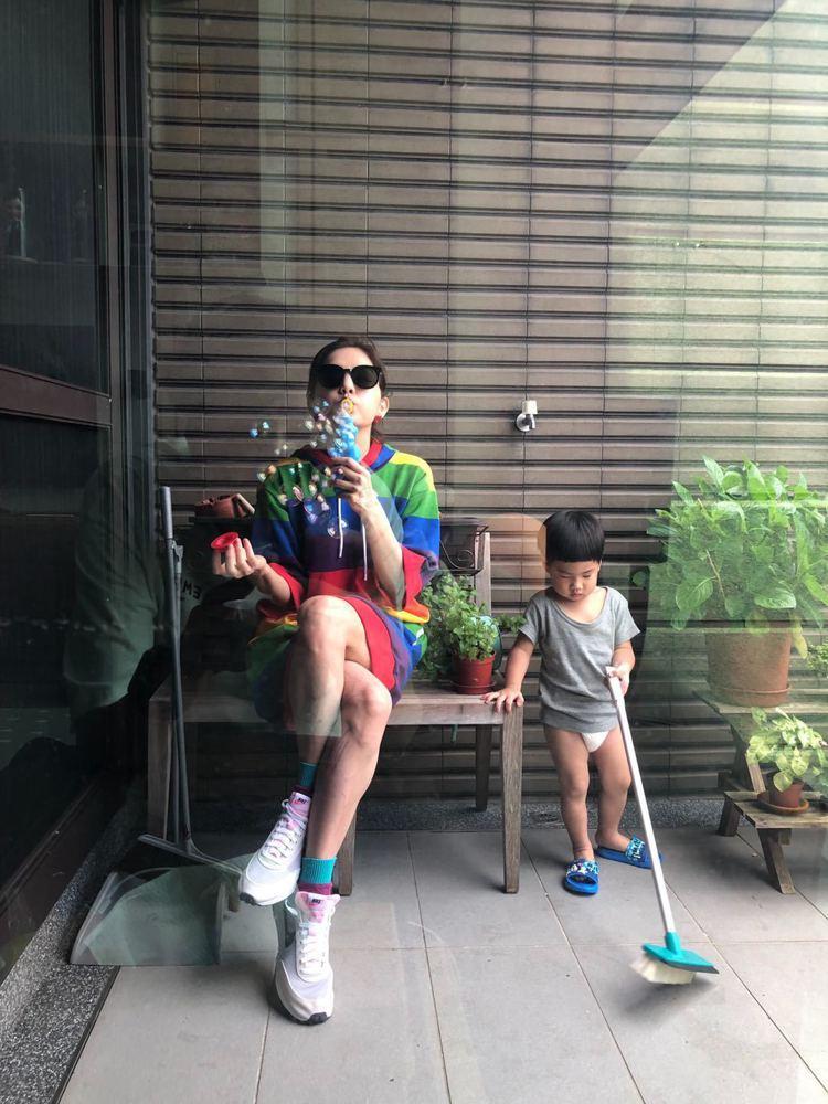 ELLA身穿MICHAEL KORS彩虹連帽洋裝,和勁寶一起在陽台玩耍。圖/MI...