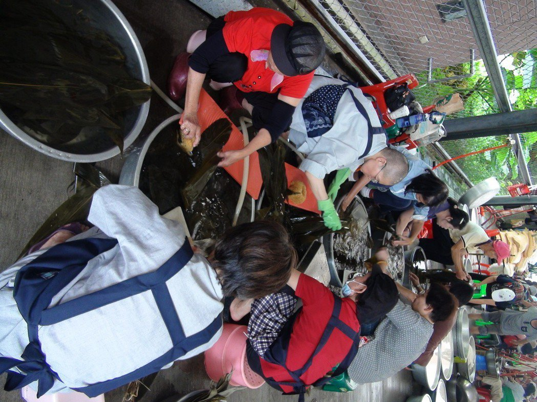 志工在洗粽葉、備料及包粽的過程中,也不忘唸佛,希望吃到的民眾都能健康快樂。記者余...