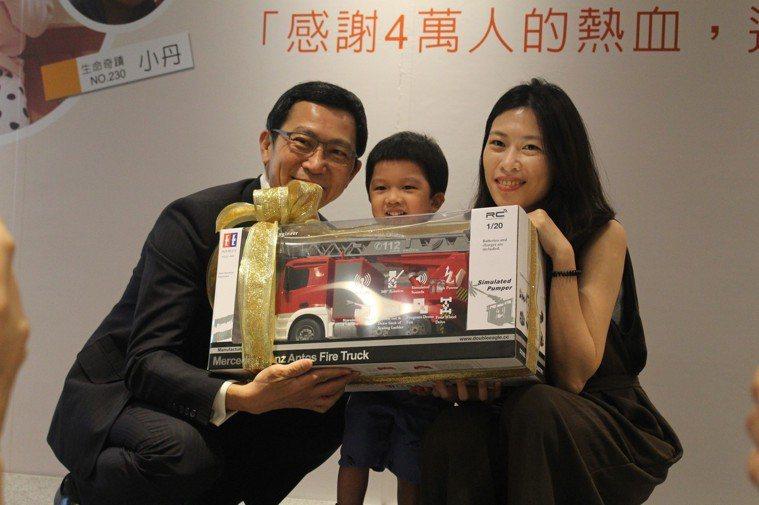 訊聯生技董事長蔡政憲(左)以小丹(中)最愛的玩具車作為禮物,慶祝小丹移植順利。記...