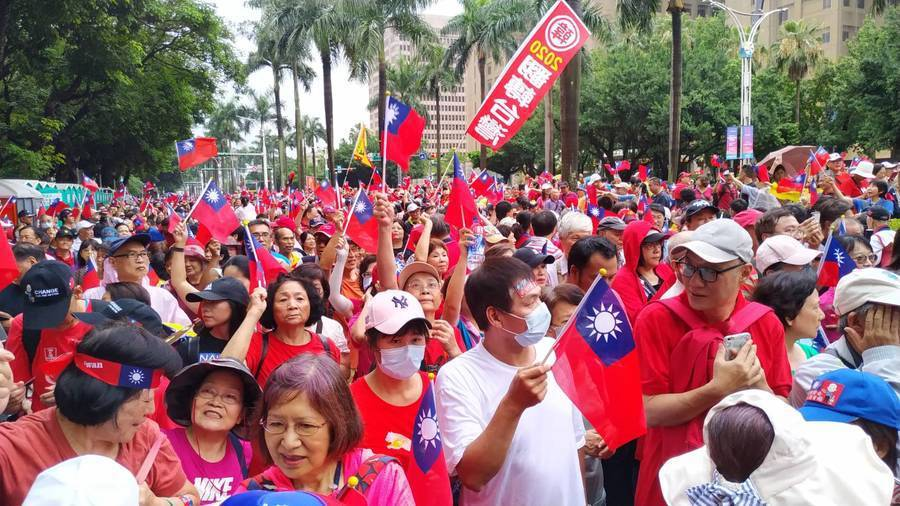中午時分,身穿紅衣的民眾陸續往凱道集結,一群一群揮著國旗,有的陣勢中有自備大鼓小...