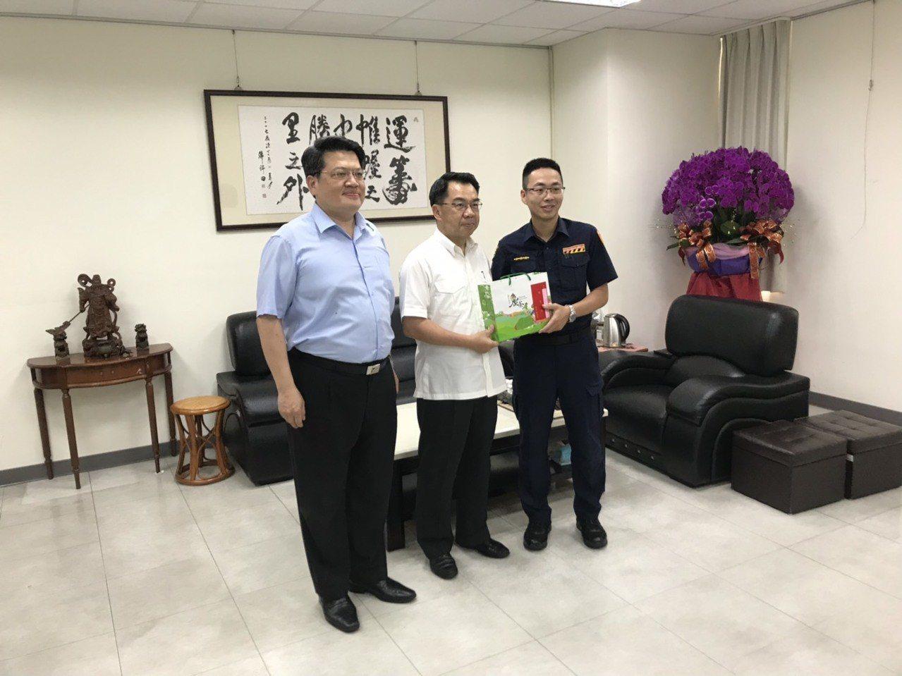 市警局局長楊源明(中)頒發「交安茶」給警員王建智(右),感謝王員的辛勞。記者林佩...